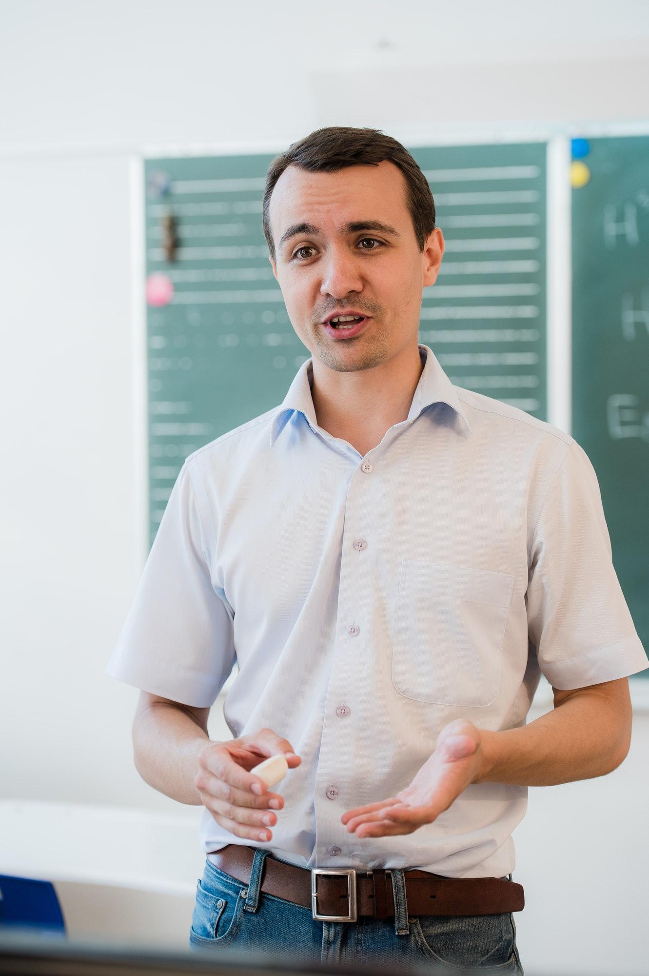 young-teacher-near-chalkboard-in-school-classroom-talking-to-class.jpg